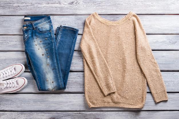 Blauwe jeans en beige pullover. sweatshirt op grijze houten achtergrond. lente casual outfit voor dames. beste artikelen in showroom.