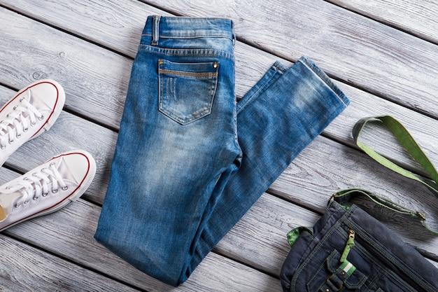 Blauwe jeans en denim portemonnee. witte canvasschoenen en jeans. showcase in jeansopslag. seizoensverkoop met kortingen.