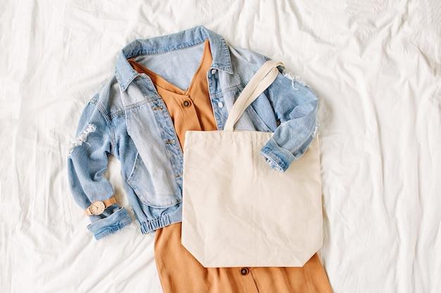 Blauwe jeansjas en beige jurk met draagtas op wit bed. stijlvolle herfstoutfit voor dames. trendy kleding met witte eco-tas mockup. plat lag, bovenaanzicht.