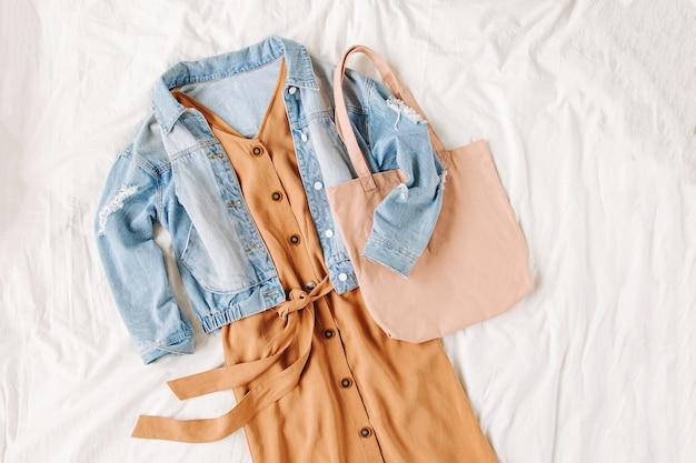 Blauwe jeansjas en beige jurk met draagtas op wit bed. stijlvolle herfstoutfit voor dames. trendy kleding. plat lag, bovenaanzicht.