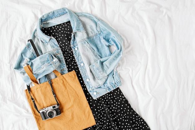 Blauwe jeansjas en zwarte jurk met draagtas en fotocamera op wit bed. stijlvolle herfst- of lente-outfit voor dames. trendy kleding. plat lag, bovenaanzicht.