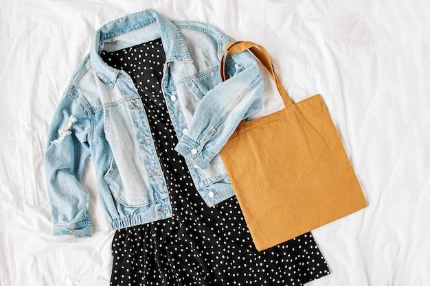 Blauwe jeansjas en zwarte jurk met draagtas op wit bed. stijlvolle herfst- of lente-outfit voor dames. trendy kleding. plat lag, bovenaanzicht.
