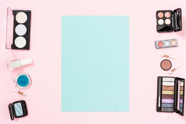Blauwe kaart met kopie ruimte voor het schrijven van de tekst met make-up cosmetische producten op roze achtergrond