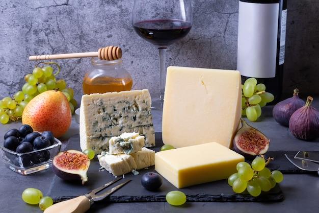 Blauwe kaas en parmezaanse kaas op een zwarte plank, fruit, wijn en honing. detailopname.
