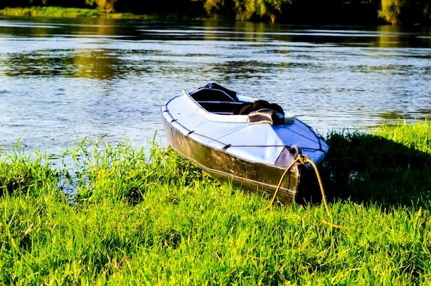 Blauwe kajak afgemeerd aan de oever van de rivier, close-up shot.