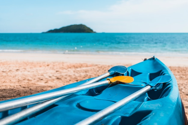 Blauwe kajak op zandige kust