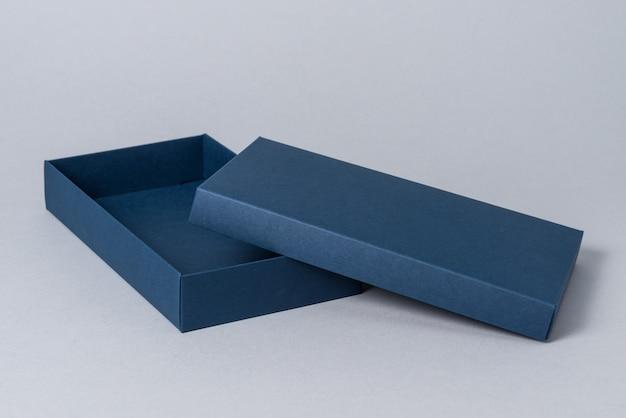 Blauwe kartonnen geschenkdoos met deksel, op grijze achtergrond