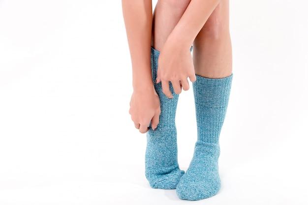 Blauwe katoenen sokken aan de voeten van een mooie vrouw. geïsoleerd op witte achtergrond studio verlichting