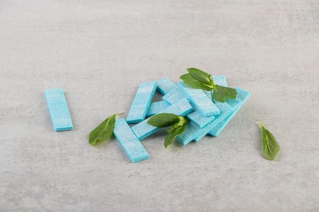 Blauwe kauwgom met muntblaadjes op een stenen tafel.