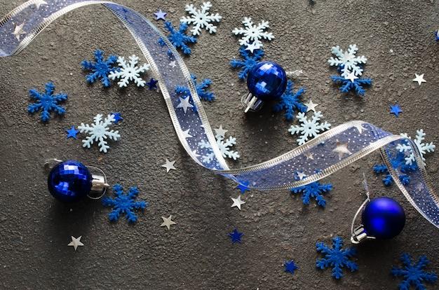 Blauwe kerst. krullend lint met decoratieve ballen en sneeuwvlokken.