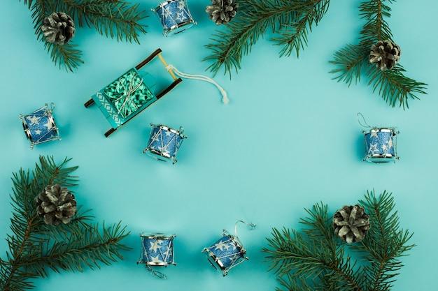 Blauwe kerstachtergrond met vuren takken en kegels, kerstspeelgoed voor decor, sleeën met een geschenk, traditionele kersttrommels. bovenaanzicht.
