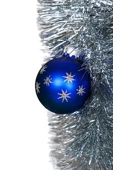 Blauwe kerstbal op de kerstslinger - geïsoleerd