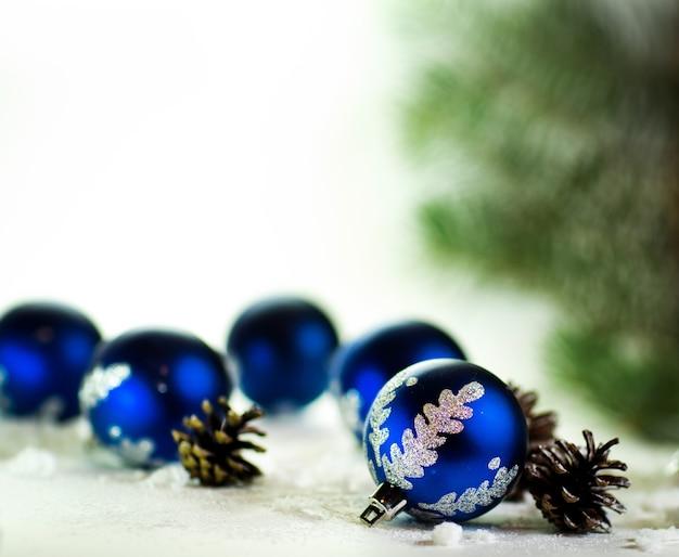 Blauwe kerstballen op witte achtergrond met dennenappels