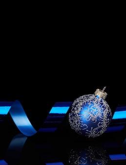 Blauwe kerstmisbal met boog op glanzende weerspiegelende zwarte achtergrond