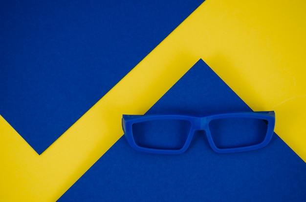 Blauwe kinderen bril op blauwe en gele achtergrond