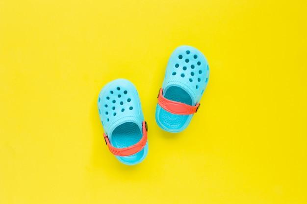 Blauwe kinderen rubberen sandalen op gele achtergrond.