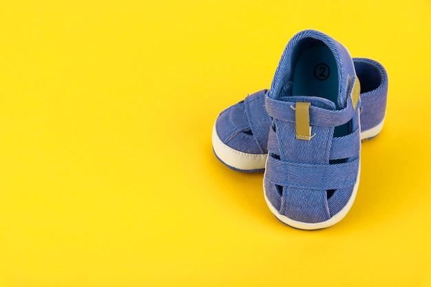 Blauwe kindersandalen voor een jongen op een gele