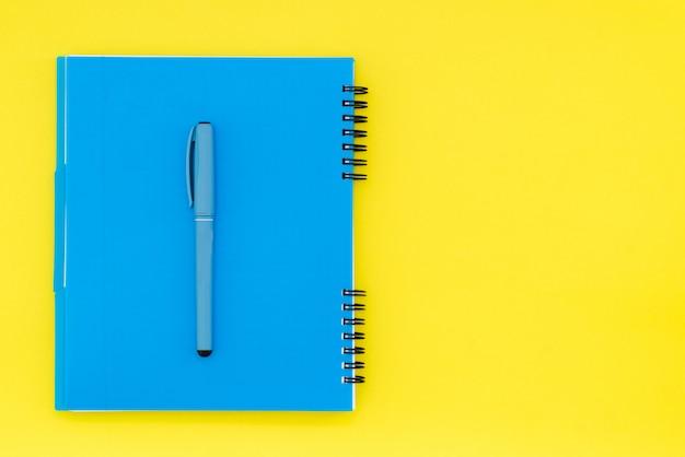 Blauwe kladblok op een gele achtergrond met een plek voor tekst. geïsoleerd op een gele blocnote als achtergrond.