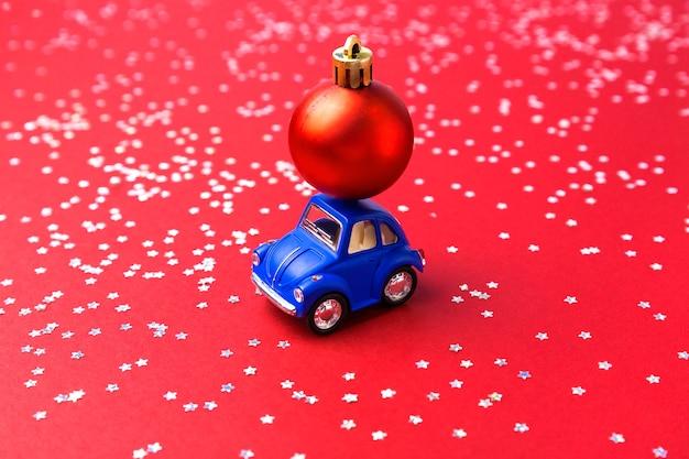 Blauwe kleine speelgoedauto met kerstversiering op rode achtergrond. kerstmis of nieuwjaar viering concept.