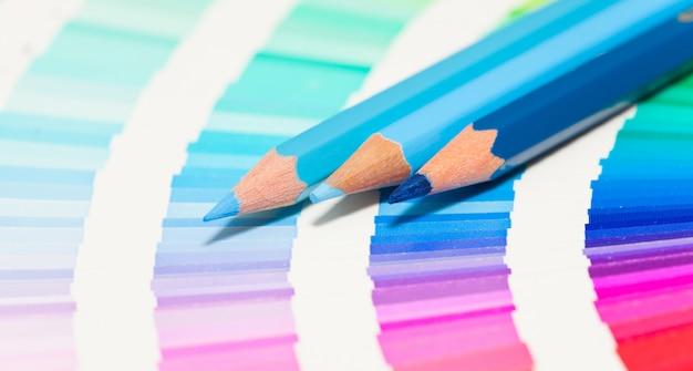 Blauwe kleurpotloden en kleurenkaart van alle kleuren