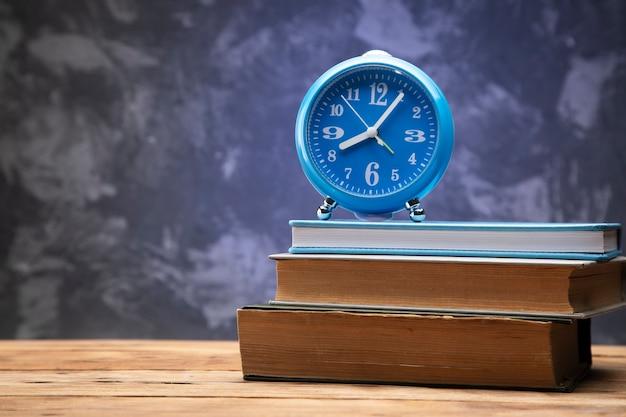 Blauwe klok op de boeken op houten tafel