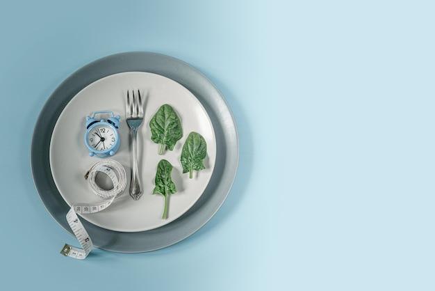 Blauwe klok, vork, spinaziebladeren en meetlint op grijze plaat, dieet en intermitterend vastenconcept