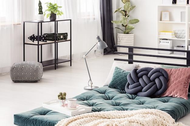 Blauwe knoop kussen op groene futon in lichte slaapkamer interieur met gedessineerde poef en lamp and