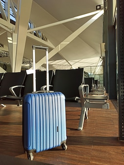 Blauwe koffer in een lege luchthaven