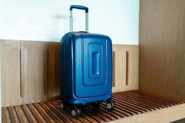 Blauwe koffer in lichte hotelkamer met bruine houten details. kopieer ruimte