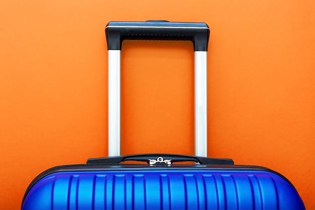 Blauwe koffer op oranje achtergrond kopie ruimte voor tekst. reis concept.