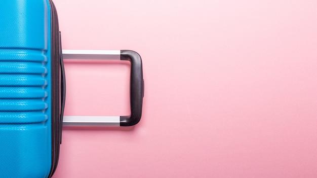 Blauwe koffer op pastel roze. creatieve zomervakantie, vakantie, reizen concept