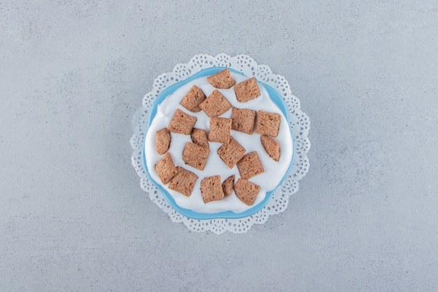 Blauwe kom chocoladepads cornflakes met roomschuim