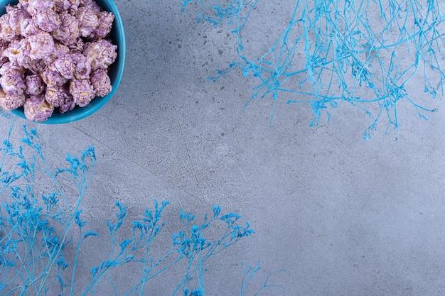 Blauwe kom gekonfijte popcorn naast blauwe decoratieve takken op marmeren oppervlak