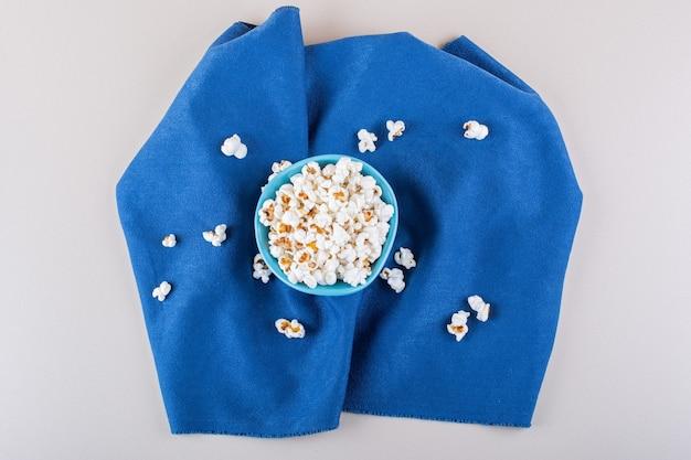 Blauwe kom gezouten popcorn voor filmavond op witte achtergrond. hoge kwaliteit foto