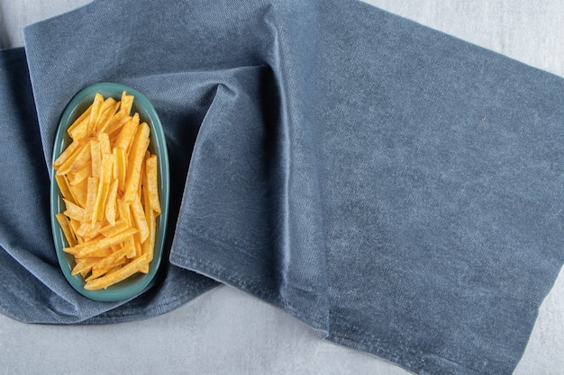 Blauwe kom krokante aardappelsticks op blauwe doek.