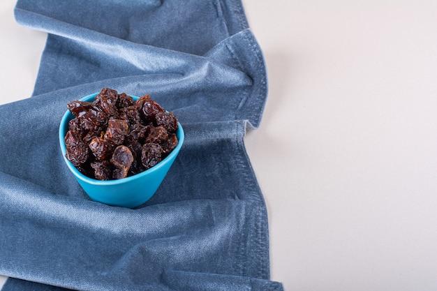Blauwe kom met gedroogde biologische pruimen geplaatst op een witte achtergrond. hoge kwaliteit foto