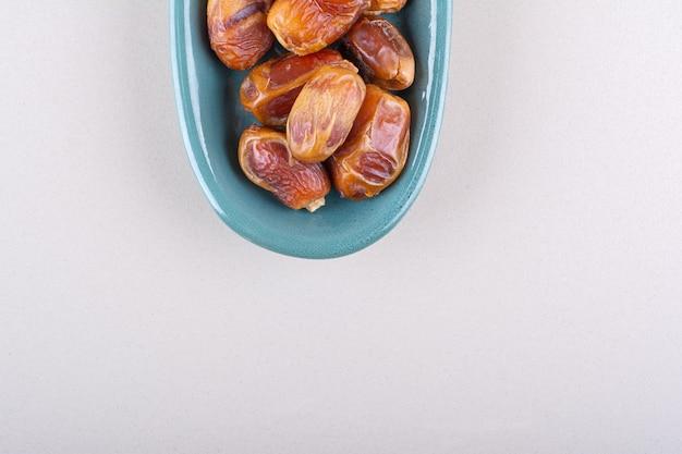 Blauwe kom met gedroogde smakelijke dadels op witte achtergrond. hoge kwaliteit foto