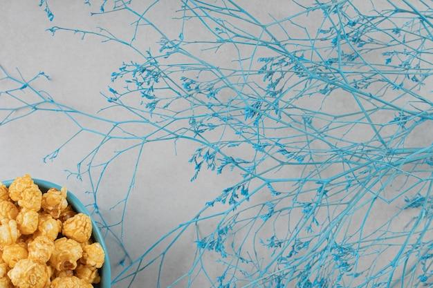 Blauwe kom met karamel op smaak gebrachte popcorn naast decoratieve takken op marmeren achtergrond.