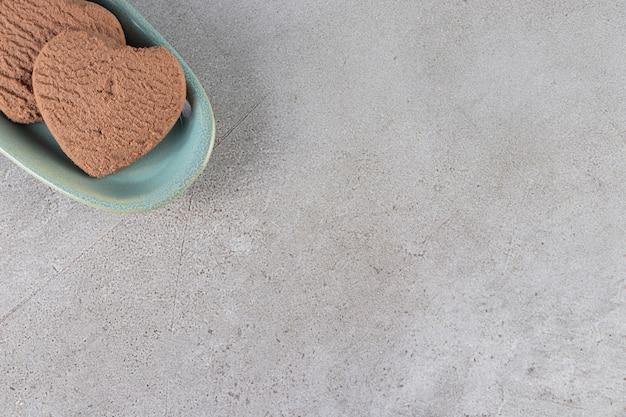 Blauwe kom met knapperige chocoladekoekjes op stenen tafel.