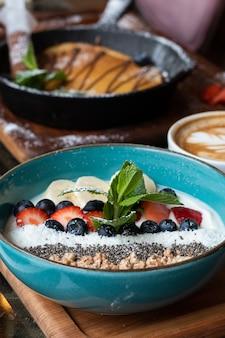Blauwe kom met ontbijtgranen en verschillende heerlijke vruchten