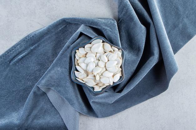 Blauwe kom pompoenpitten met blauwe doek op stenen achtergrond.