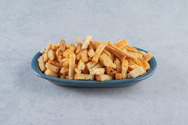 Blauwe kom smakelijke krokante crackers op stenen achtergrond.