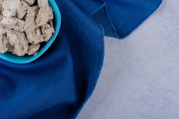 Blauwe kom smakelijke zonnebloemhalva op steen.
