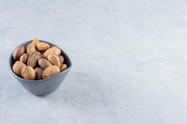 Blauwe kom vol gepelde amandelen en walnoten op steen.