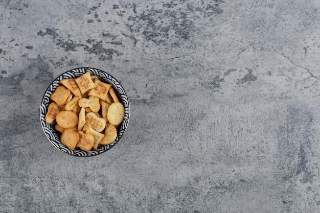 Blauwe kom vol met verschillende gezouten crackers op marmeren achtergrond.