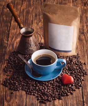 Blauwe kop koffie, bonen, turkse koffiepot en ambachtelijke papieren zakzak op houten achtergrond
