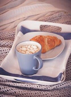 Blauwe kop koffie met marshmallow en croissant op een witte dienblad