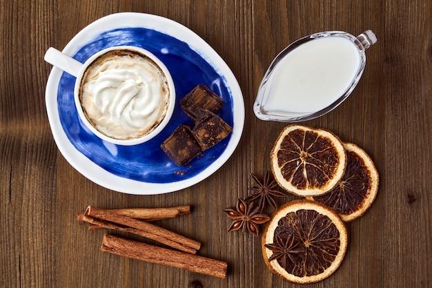 Blauwe kop koffie met roomchocolade en kruiden op een donkere houten tafel
