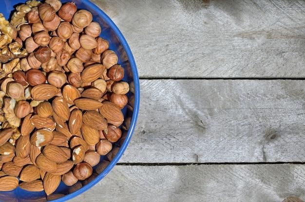 Blauwe kop met noten op een houten achtergrond