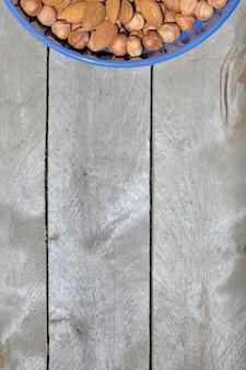 Blauwe kop met noten op een houten tafel